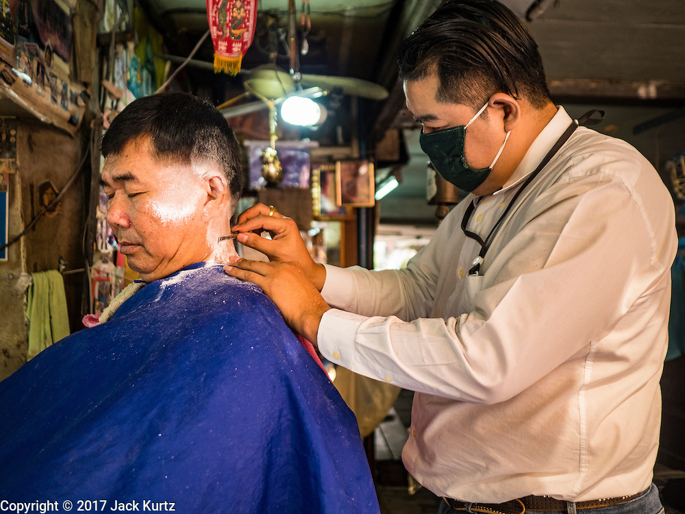 "06 FEBRUARY 2017 - BANGKOK, THAILAND:  A barber gives a customer a shave in a small barbershop in what used to be known as Kalabok Market under the Phra Khanong Bridge in the Phra Khanong district of Bangkok. Kalabok is the Thai word for hairdresser and the market was called Kalabok because there were many barbershops and hairdressers under the bridge. In 1985, the city changed the name of the market to ""Singha Market."" There are still about 10 small men's barbershops, most with just one barber, and four women's salons, most with one hairdresser,  under the bridge.     PHOTO BY JACK KURTZ"