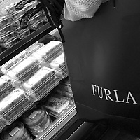 A Japanese tourist, holding a shopping bag from the 'Furla' designer brand store, shops for sandwiches in a convenience store in Tumon, Guam, on Saturday, Mar. 10, 2007.  Sometimes known as 'America in Asia', Guam is a popular destination for Japanese tourists ( accounting for approx 90% of the island's visitors) with average visitor numbers from Japan approaching 1million.  The island, a 3.5 hour flight from Japan, has more than 20 large hotels and numerous duty-free shopping malls catering to the Japanese tourists predilection for designer brand name goods, as well as golfing and other water based entertainment features. In 2007-2008 US military personal currently stationed in the Japanese Okinawan Islands will relocate their bases and operations  to Guam, helping to stabilise the island's economy which suffered after tourism decreased in recent years due to a  fear of flying by Japanese post 9-11 World Trade Centre disaster, a 2003 typhoon and the SARS disease outbreak in Asia.