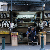 A man sits at a stall where he sells ladies head scarves in the Mea Sharim neighborhood of Jerusalem