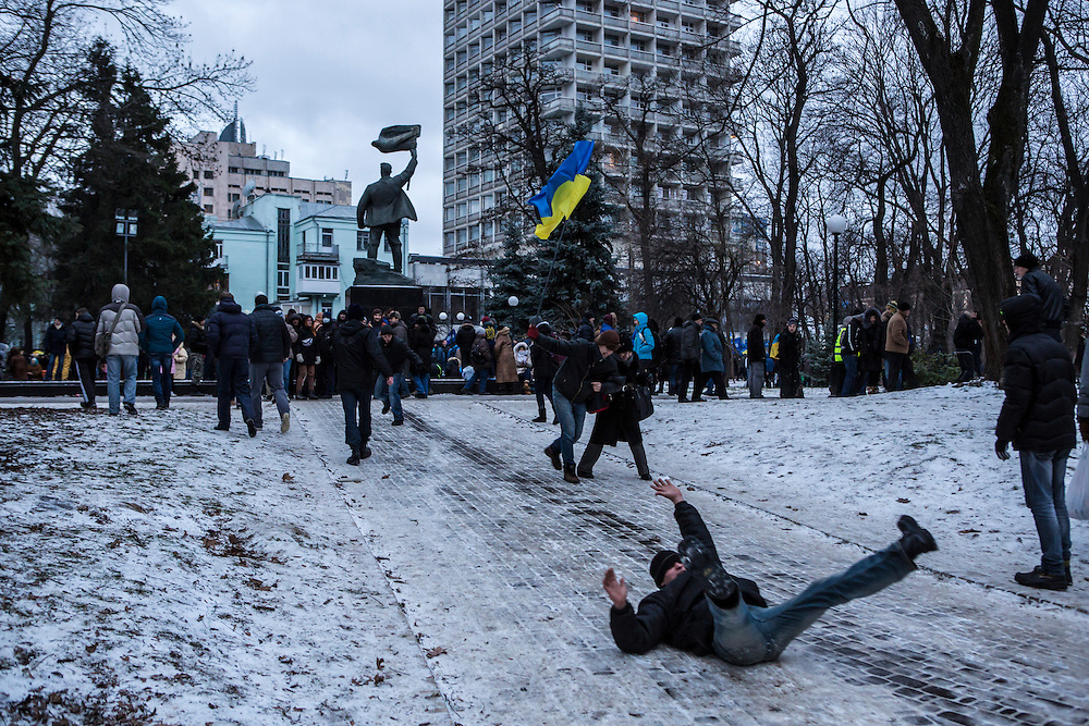 KIEV, UKRAINE - DECEMBER 8: An anti-government protester slides down an icy path in a park the site of a rally held by the ruling Party of Regions in support of the government and Ukrainian president Viktor Yanukovych on December 8, 2013 in Kiev, Ukraine. Thousands of people have been protesting against the government since a decision by President Yanukovych to suspend a trade and partnership agreement with the European Union in favor of incentives from Russia. (Photo by Brendan Hoffman/Getty Images) *** Local Caption ***