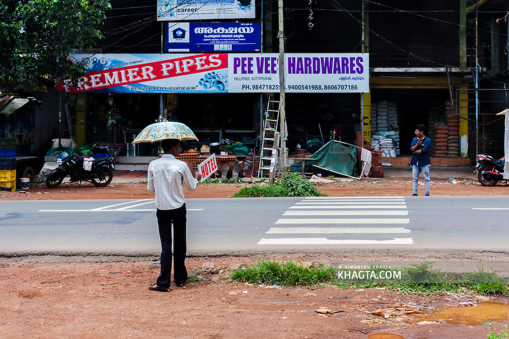 A man holding a HOTEL sign by the highway in Kerala