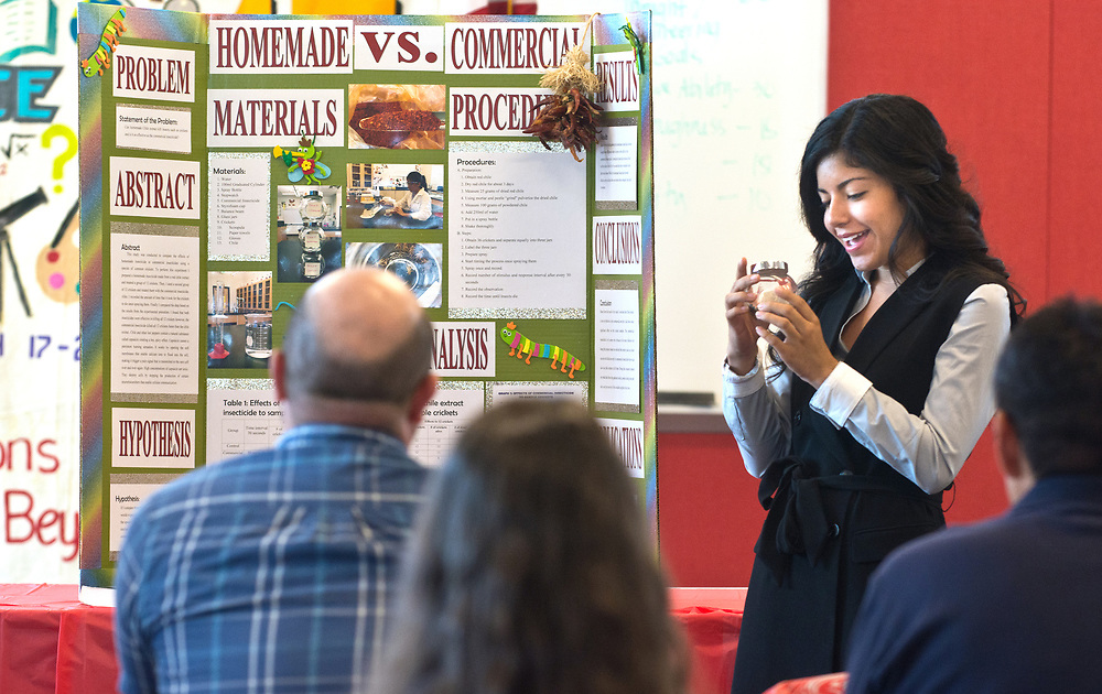 mkb032317/metro/Marla Brose --  Monica Montano, an AP Chemistry student and a senior at Bernalillo High, looks at a container of dead crickets that she used to test her homemade red chile insecticide for the science fair project that she was presenting to a panel of judges in the school's library, Thursday, March 23, 2017 in Bernalillo, N.M. (Marla Brose/Albuquerque Journal)