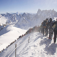 Skiers and climbers descend from the Aguille du Midi tram station to the Valle Blanche glacier.