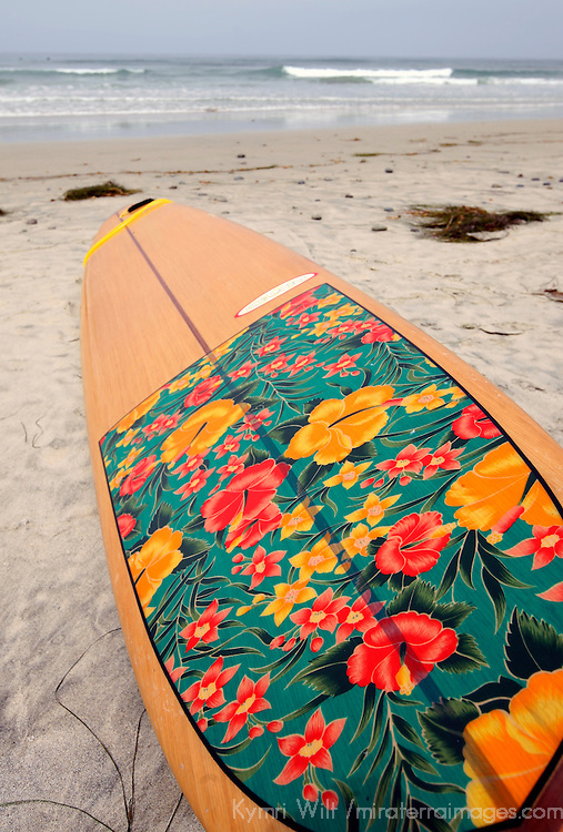 Woman's surfboard on the beach with ocean and waves.