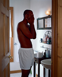 man waking up in the morning and covering his face while standing in the bathroom