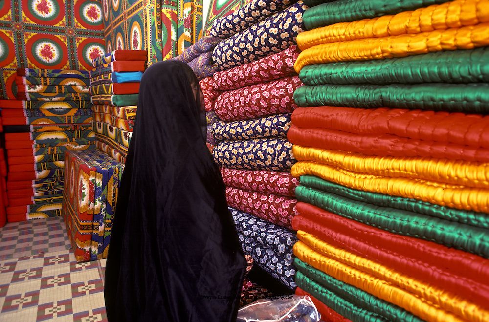 Woman shopping for bedding in the souq.  There are colorful futons, blankets, quilts to choose from. Sakaka, Saudi Arabia