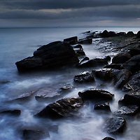 A long exposure of the sea swirling around rocks at twilight, the Fife coastline, Scotland.