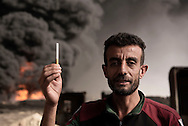 Iraq, Qayyara: On October 2016, Makhmoud, behind him one of the still burning wells.<br /> &quot;The first time I was surprised while smoking, they gave me a fine of 300,000 dinars, they told me it was just a warning, and the next time they would cut my head. <br /> The same people who forbade us to smoke burned our main wealth, oil.<br /> They exploited all our oil and sold it on the black market. <br /> Today we have nothing, no house, no job, nor the wealth of the country: oil&quot;. Alessio Romenzi