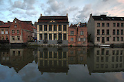 Reflections at dusk of buildings in the River Leie in Ghent, Belgium