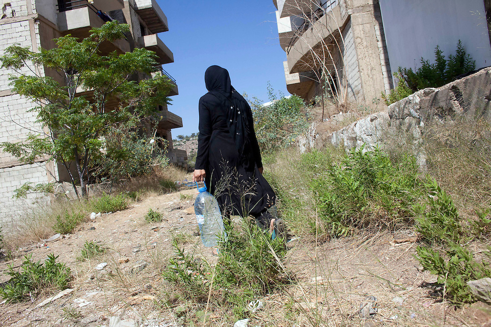 05/07/2013 near Damour, Lebanon: A Syrian mother collects water for cooking. Many of the flats in the vacation-home development lack basics like electricity and running water. Estimates have placed the number of Syrian refugees in Lebanon at well over 500,000 people.