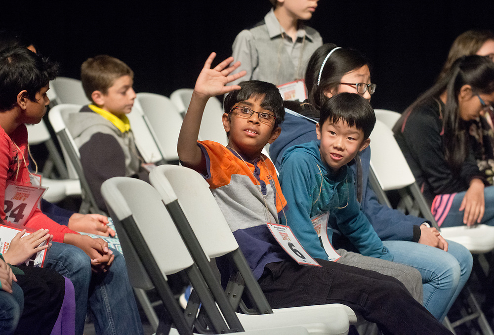 Akilan Sankaran, center, a Manzano Day School 4th grader, waves to his family before winning the 2017 New Mexico Spelling Bee at Sandia Prep, Saturday, March 18, 2017. (Marla Brose/Albuquerque Journal)