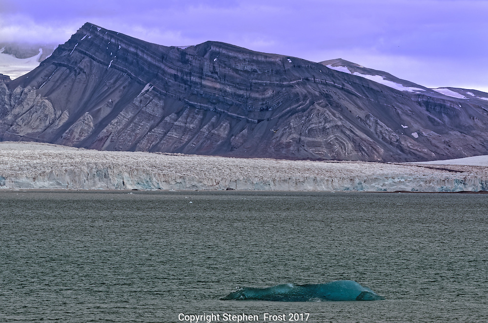 Glacier in Svalbard, with small floating iceberg.<br />