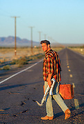 man walking with a saxophone and vintage suitcase down an empty road in the California desert