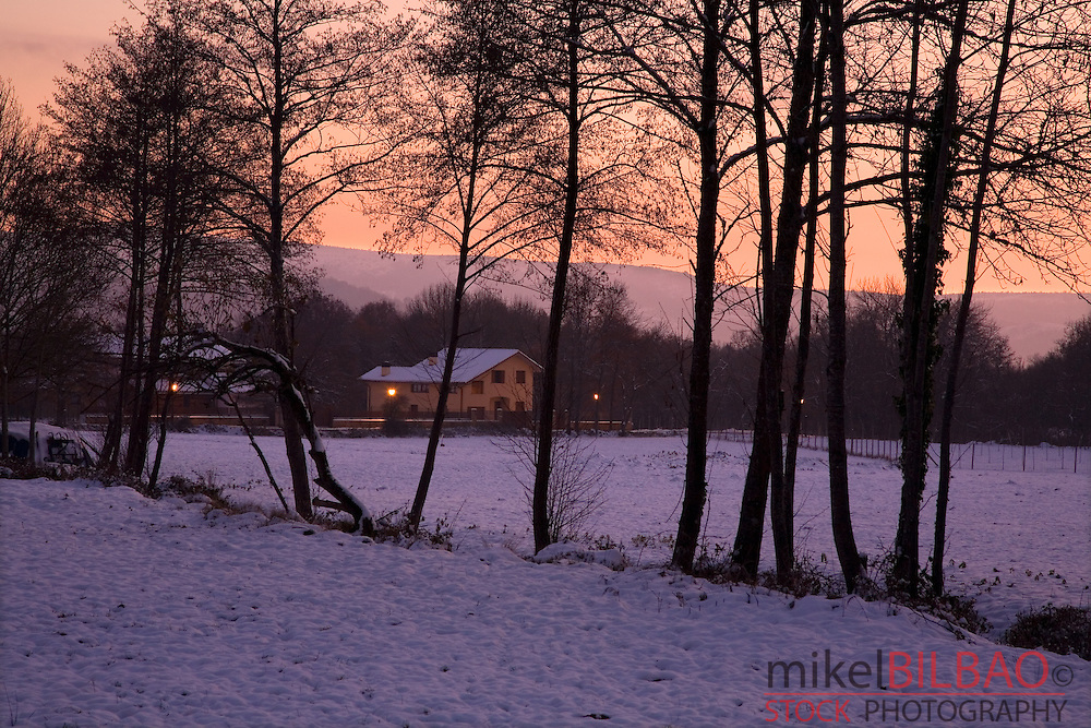 trees and house in a snow covered landscape on sunset. Gorbea Natural Park. Alava, Basque Country, Spain, Europe.