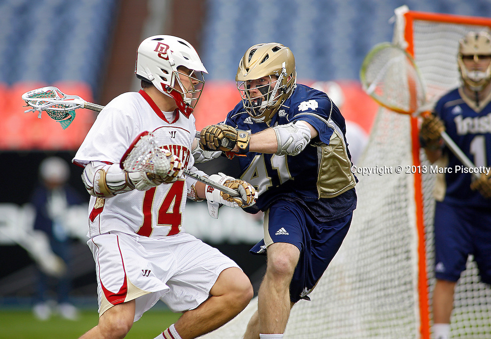 SHOT 3/16/13 3:33:37 PM - Denver's Wes Berg #14 looks to pass to a teammate in front of Notre Dame's Quinn Cully #41 during their college lacrosse game at the Whitman's Sampler Mile High Classic at Sports Authority Field at Mile High in Denver, Co. on Saturday March 16, 2013. Notre Dame won the game 13-12 in overtime. (Photo by Marc Piscotty / © 2013)