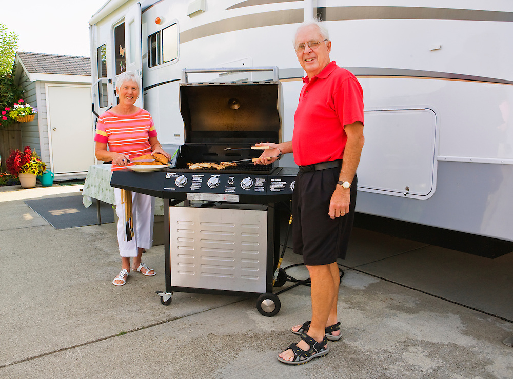 A portrait of a mature couple barbequing in front of their mobile home trailer.