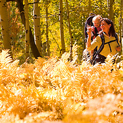A mother with her infant daughter in a child backpack enjoying the autumn colors in an aspen grove in Utah's Wasatch Mountains.