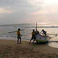 Fishermen beaching their boat. Santhome Beach and adjoining Marina Beach in Chennai, India were hit hard by the 2004 Tsunami. Fishermen and their families were the main victims living in their lightweight huts on the long and flat beaches of the area. All structures within 300 metres of the sea have now been banned and any left standing after the Tsunami were demolished. The fishermen and their families have now been relocated to government blocks of flats which has become a Santhome slum for fishermen and their families.