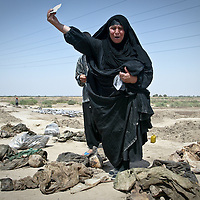 An Iraqi Shiite woman weeps after discovering the identity card of a relative during a search for the remains of loved ones pulled from a mass grave in Mahawil, Iraq. The mass grave containing over 3,000 bodies was discovered near Hilla in central Iraq. Hundreds of families traveled to the site with the hope of locating the remains of relatives missing since the 1991 Shiite uprising. May 2003.