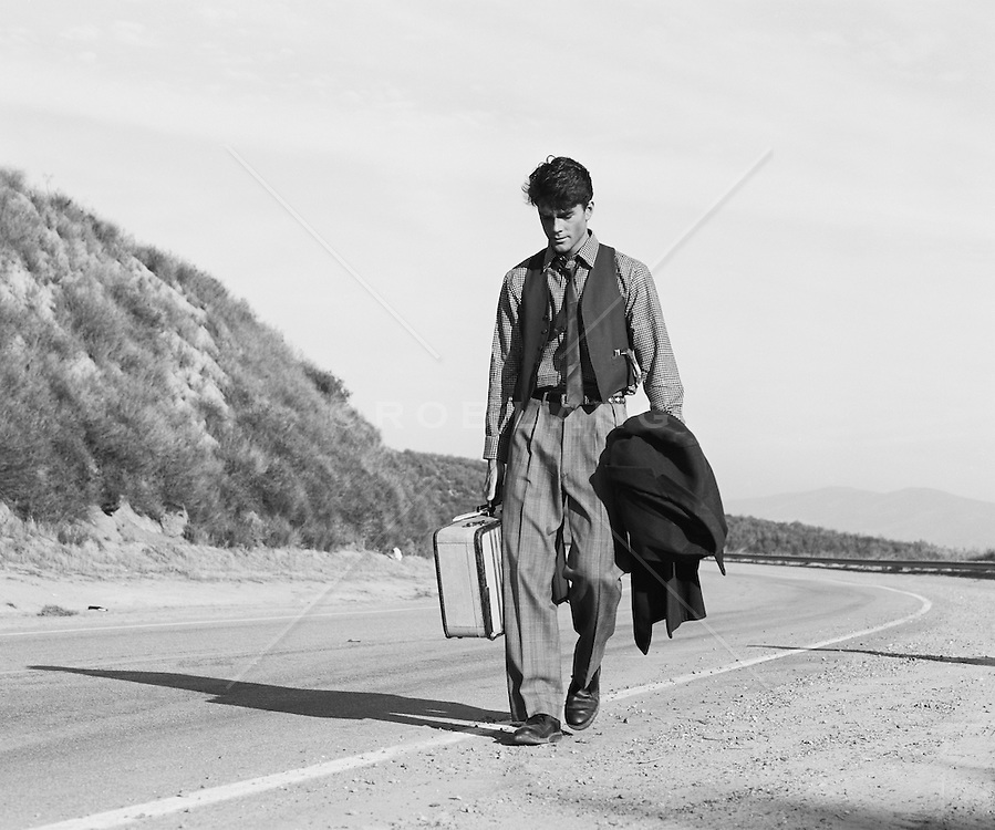Man in 1940's clothes walking on the roadside in California
