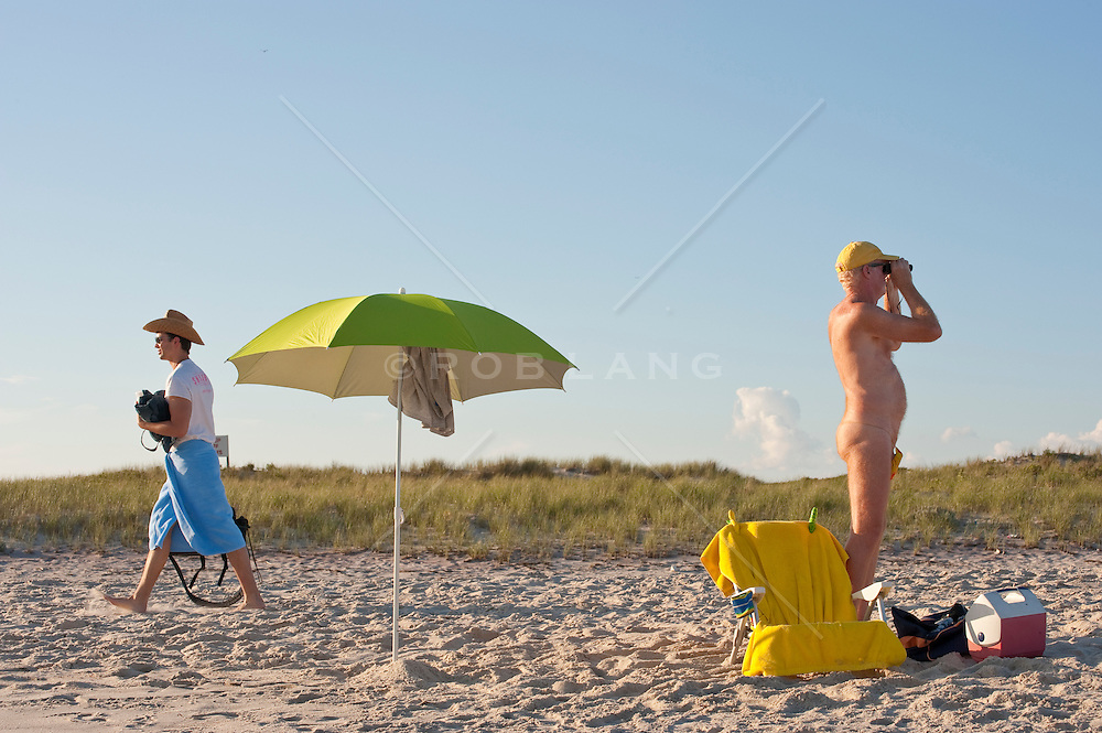 man in a g-string looking through binoculars while a man in a cowboy hat walks by at the beach