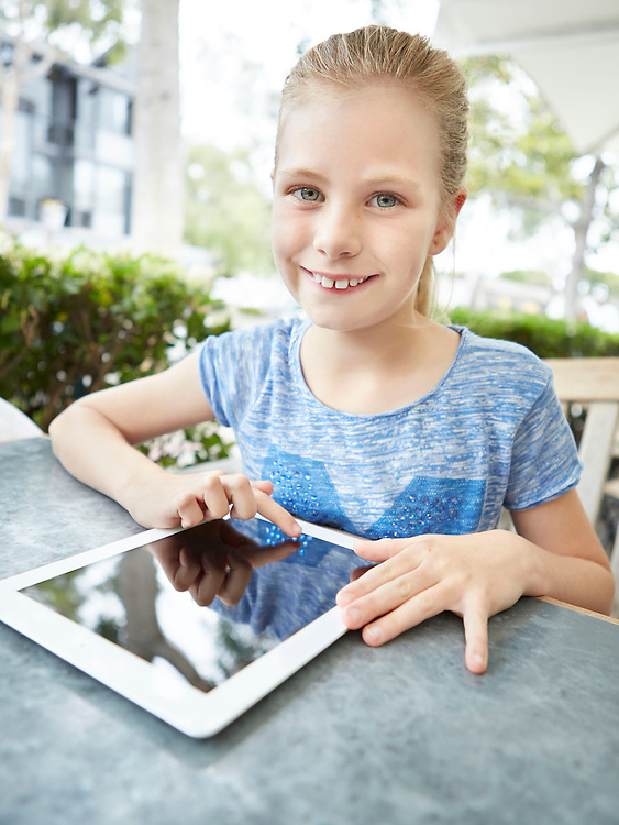 Lifestyle image of smiling kid with iPad tablet