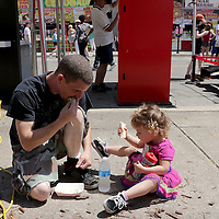 James Carver has lunch with his daughter Olivia Carver, 2, behind the vendors on Water Street Sunday during the North Carolina Azalea Festival. (Jason A. Frizzelle)