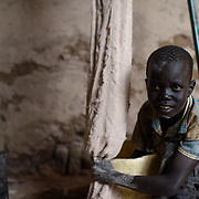 Emmanuel Ohisa at work in a sorghum mill in the village of Kudo in Eastern Equatoria in South Sudan on 8 August 2014.