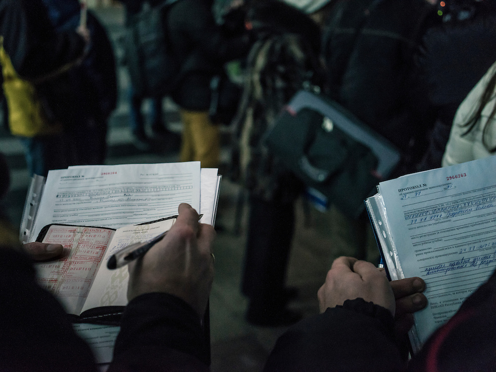 Police fill out legal forms to fine Mikalai Statkevich, a former opposition presidential candidate and political dissident, for organizing an illegal rally to commemorate the nineteenth anniversary of a referendum which enshrined authoritarian changes in Belarus's constitution on Tuesday, November 24, 2015 in Minsk, Belarus.