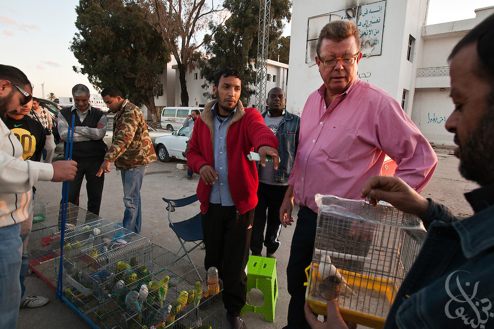 Dr. Ronald Meinardus (l), Regional Director of the Friedrich Naumann Foundation for Liberty (FNF) speaks with bird vendors at an outdoor market in  Benghazi, Libya December 16, 2011. The market occupies the space of a looted military base that once stood as the city's central garrison for troops and authorities loyal to former leader Muammar Gaddafi. (Photo by Scott Nelson, for Der Spiegel)