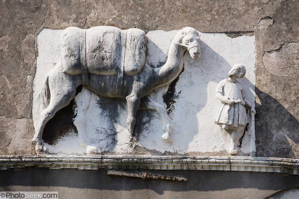 """A bas-relief of a man leading a laden camel decorates the facade of Palazzo Mastelli (or Palazzo del Cammello, """"House of the Camel""""), along Rio della Madonna dell'Orto, in Cannaregio sestiere, Venice, Italy, Europe. This was the former home of the Mastelli mercantile family. Venice (Venezia), founded in the 400s AD, is the capital of Italy's Veneto region, named for the ancient Veneti people from the 900s BC. The romantic City of Canals stretches across 100+ small islands in the marshy Venetian Lagoon along the Adriatic Sea between the mouths of the Po and Piave Rivers. The Republic of Venice was a major maritime power during the Middle Ages and Renaissance, a staging area for the Crusades, and a major center of art and commerce (silk, grain and spice trade) from the 1200s to 1600s. The wealthy legacy of Venice stands today in a rich architecture combining Gothic, Byzantine, and Arab styles. Venice and the Venetian Lagoon are honored on UNESCO's World Heritage List."""