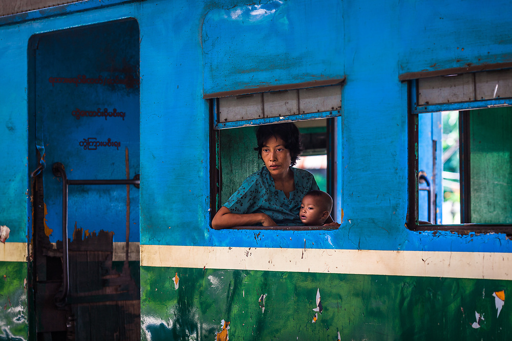 A woman and child peer out of a train waiting for departure at central station, Yangon, Myanmar, formerly known as Burma.