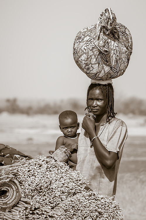 Portrait of a Peuhl woman on the move with her child and worldly possessions in northern Burkina Faso. The Fulani or Peuhl are nomadic herdsmen of the Sahel region of West Africa.