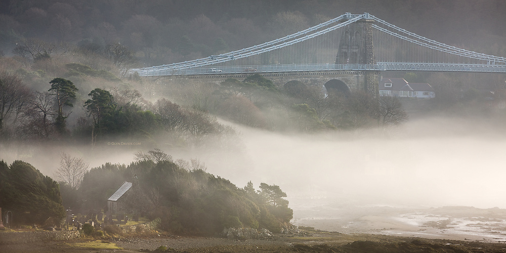 An eary morning fog rolls in off the sea, shrouding the idyllic church and graveyard of Ynys St Tysilio, Anglesey. The 100 foot high Menai Suspension Bridge completed in 1826 by Thomas Telford stands proud of the low lying fog.