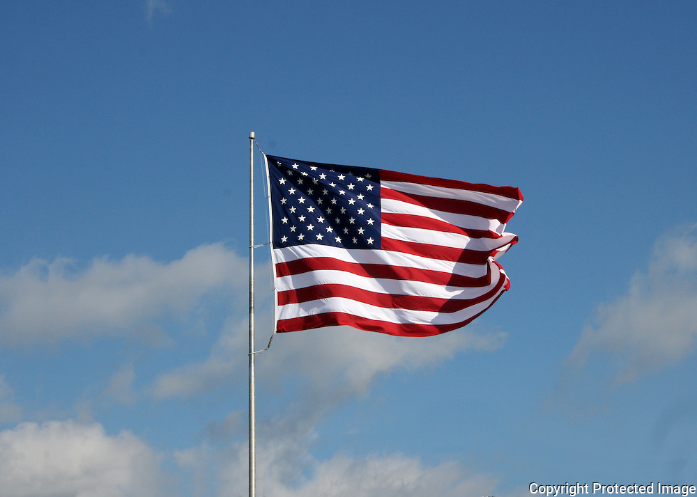 A large American Flag flying in a stiff breeze under a brilliant blue sky.