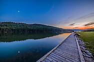 The quarter Moon reflected in the waters of Reesor Lake, Alberta in Cypress Hills Interprovincial Park. Taken on July 5, 2014. This is with the 14mm Rokinon lens and Canon 6D at ISO800. This is a high dynamic range stack of 6 exposures from 1/15 to 0.6 seconds taken just before using the camera to take a motion control time-lapse. The Moon was in conjunction with Mars (right of Moon) and Spica (left of Moon) but in the bright twilight they are not showing up here.