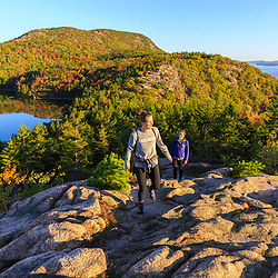 "Two women hiking on ""The Beehive"" in fall in Maine's Acadia National Park.`"