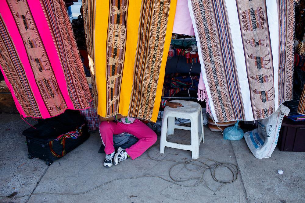 FEIRA DA KANTUTA - Menina descansa nos fundos de uma barraca de malhas bolivianas da feira boliviana na praça Kantuka, no bairro Canindé, em São Paulo. 26/06/2016