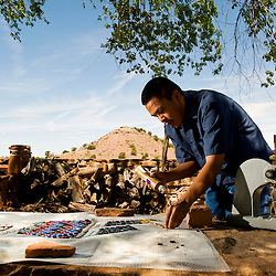 Philander Begay works on a yei bi cheii mosaic at Hubbell Trading Post on Thursday. Begay is learning a new technique from artist in residence Robin Brailsford that he hopes to combine with his native art.