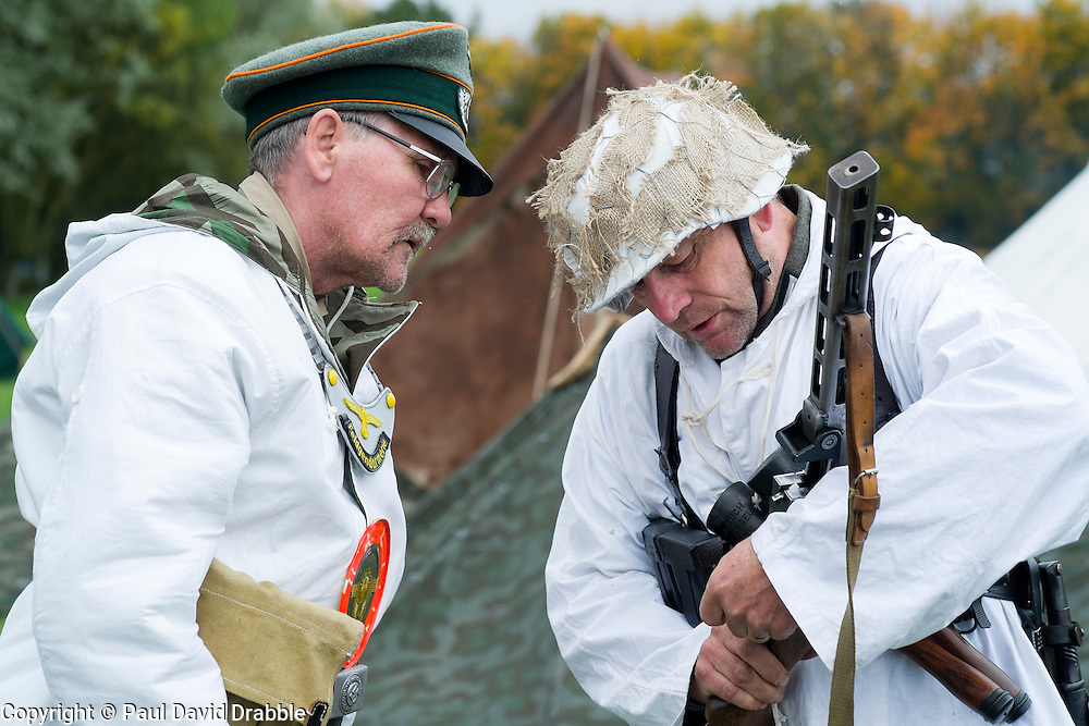 Re-enactors portraying German troops operating on the Russian Front examins a soviet PPS41 Sub machine gun. On the left is a  feldgendarme (field Policeman). He can be identified by the Orange trim or Waffenfarbe seen on his hat and the Goget around his neck. both are wearing white winter camouflage which is reversible to splinter pattern camouflage.<br /> Pickering Showground 1940 Wartime Weekend 7/18 October 2015<br />  Image &copy; Paul David Drabble <br />  www.pauldaviddrabble.co.uk
