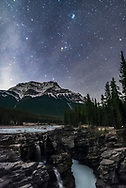 The Pleiades star cluster and the other stars of Taurus rising above Mount Kerkeslin at Athabasca Falls, in Jasper National Park, Alberta, October 22, 2016. The sky is brightening with the rising waning Moon off frame at left. Some cloud adds star glows and hazy patches to the sky. <br /> <br /> This is a stack of 15 exposures, mean combined to smooth noise, for the ground and one exposure for the sky. All are 25 seconds at f/2 with the Sigma 20mm Art lens and Nikon D750 at ISO 6400. A master dark frame of 12 darks was also stacked in with Difference mode to remove some discolouration.