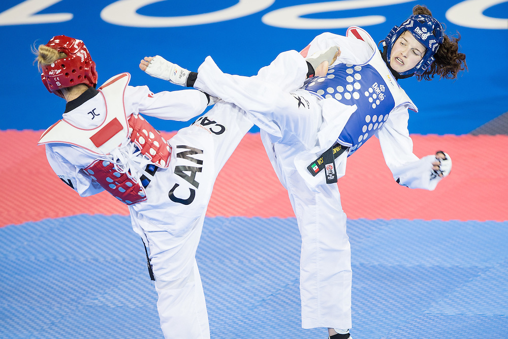 Evelyn Gonda (L) of Canada and kick Paulina Armeria of Mexico trade kicks during their semifinal contest in the women's -57kg weight class of Taekwondo at the 2015 Pan American Games in Toronto, Canada, July 20,  2015.  AFP PHOTO/GEOFF ROBINS