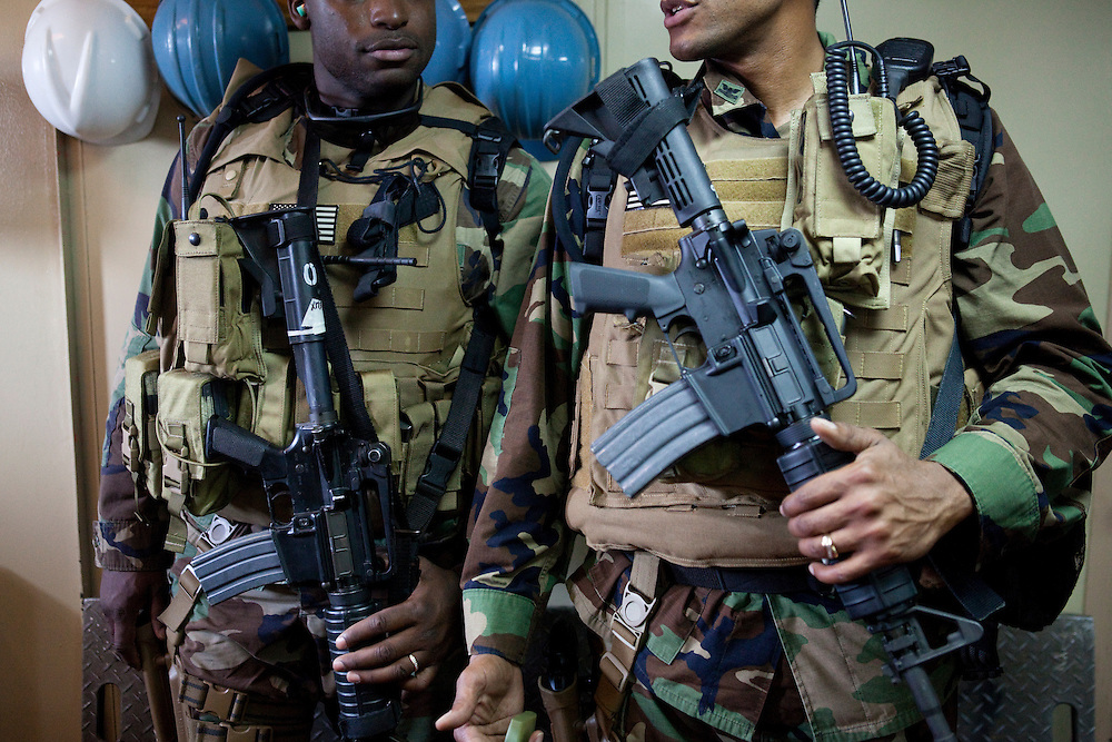 MA2 Harry St. Felix, left, and MA1 Roderick Broussard, Naval security officers, stand guard just off the flight deck of the USNS Comfort, a naval hospital ship, on Wednesday, January 20, 2010 in Port-Au-Prince, Haiti. The Comfort deployed from Baltimore, bringing nearly a thousand medical personnel to care for victims of Haiti's recent earthquake.