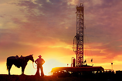 Stock photo of a cowboy standing with his horse in front of an oil and gas drilling rig at sunset in Texas
