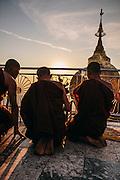 Monks prayer at sunset at Kyaiktiyo Pagoda (Golden rock)). Mon State, Myanmar