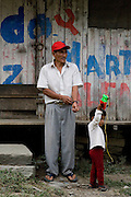A man and his son with a toy truck outside their house, adjacent to the Interoceanic Highway