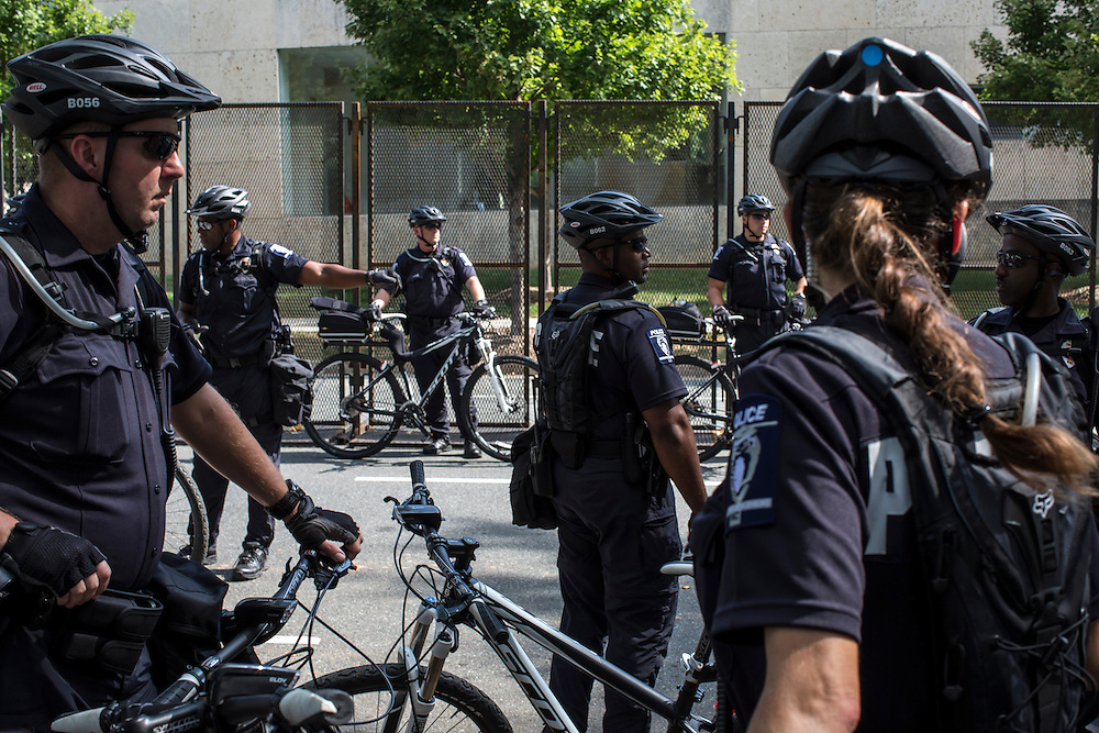 Police officers keep watch over a Labor Day parade and march passes near the security fence for the Democratic National Convention on Monday, September 3, 2012 in Charlotte, NC.