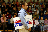 Spectators listen U.S. Democratic presidential candidate John Edwards speaks to potential voters during a campaign stop in Exira, Iowa, October 16, 2007.