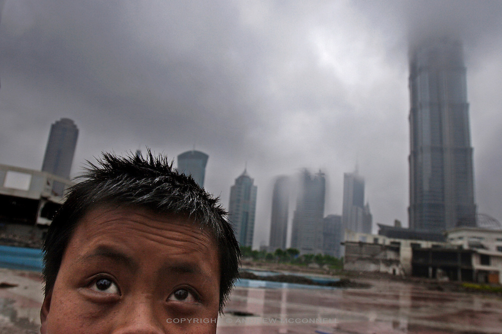 A young migrant worker surveys his surroundings in the Pudong district of Shanghai, China.