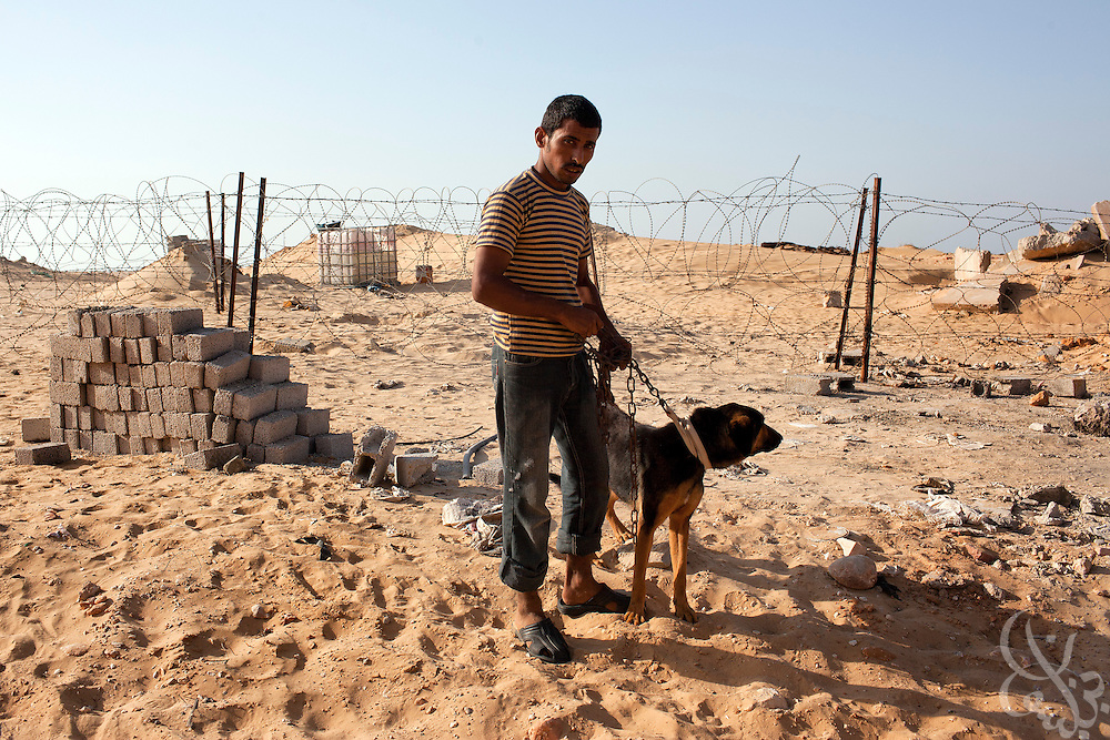 Bedouin watchman Mohamed Ouda stands guard with his dog on the perimeter of a recently bombed natural gas pumping station, one of more than a dozen located just outside the North Sinai town of Areesh, Egypt (40 kilometers from the border with Israel.) Since the Egyptian revolution, a decline in the number of police across the Sinai has resulted in a boom in the smuggling business and a spate of bombings targeting the natural gas export pipeline to neighboring Israel..Slug: Sinai.Credit: Scott Nelson for the new York Times
